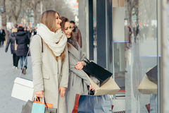 Two girls looking at show-window Royalty Free Stock Image