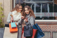Two girls looking at smart phone in front of showwindow with sal Royalty Free Stock Images