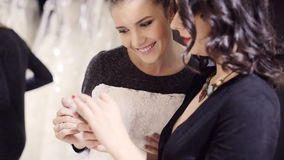 Two girls looking at a smartphone. In Bridal store stock video footage
