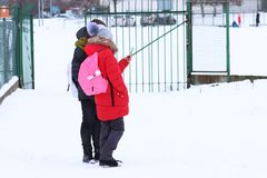 Two girls are looking into the smartphone while standing in the winter on the street covered with snow. The interest of modern royalty free stock image