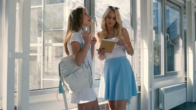 Two girls are looking at the tablet near window. Pretty girls looking at the tablet near the window. The girls are talking and speaking. The girls smiling stock footage