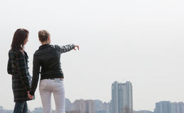 Two girls looking to a city panorama Stock Images