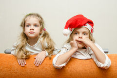 Two girls looking to left leaning back on the couch Royalty Free Stock Image