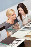 Two girls looking at window case with jewelry Stock Images