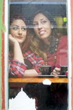 Two girls looking through the window Stock Image