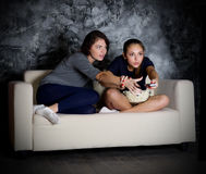 Two girls looks TV Stock Images