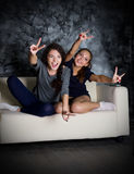 Two girls looks TV. At dark room Stock Photography