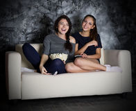 Two girls looks TV. At dark room Royalty Free Stock Photos