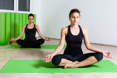 Two girls in lotus position Royalty Free Stock Images