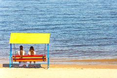 Two girls in love. Romantic couple sitting on a swing on the beach. Two girls in love Stock Image