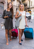 Two girls with luggage at street Stock Photo
