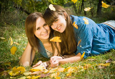 Two girls lying in autumn leaves. Outdoors Stock Images