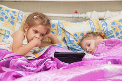Two girls lying in bed looking at a tablet computer Royalty Free Stock Photography