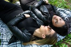 Two girls lying down on the blanket and talking in a green meadow on a spring day in nature. Girl wear sunglasses and a black jacket. Relaxation and enjoy stock photos