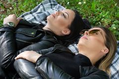 Two girls lying down on the blanket and thinking in a green meadow on a spring day in nature. Girl wear sunglasses and a black jacket. Relaxation and enjoy royalty free stock photos