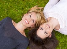 Two girls lying in the grass Royalty Free Stock Photos