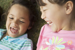 Two girls (3-5) lying on grass, laughing, close-up, overhead view Stock Photos