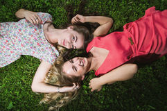 Two girls lying on the grass. Photo of two girls in dress from the top stock images