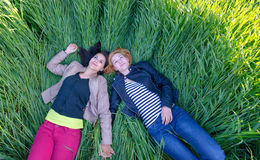 Two girls lying on grass in summer Stock Photos