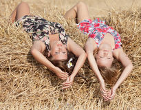 Two girls lying on hayloft Royalty Free Stock Photo