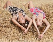 Two girls lying on hayloft Royalty Free Stock Photo