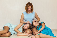 Two girls lying on his mother's lap. Stock Image
