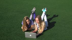 Two girls are lying on the lawn with grass using laptop. Two young beautiful girls lie on the lawn with grass using laptop stock video footage