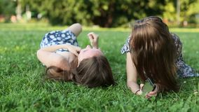 Two  girls lying on the lawn, talking and having fun. stock video