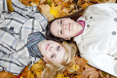 Two girls lying in leaves. Autumn Stock Photography