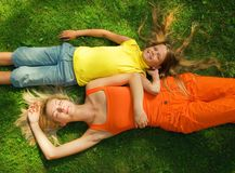 Two girls lying on a meadow Stock Images