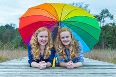 Two girls lying in nature under colorful umbrella Royalty Free Stock Image