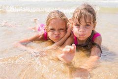 Two girls lying in shallow water and fun pretending faces looking in the frame. Two girls lying in the shallow water and fun pretending faces looking in the Stock Photo