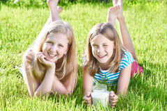 Two girls lying in sunny meadow with jug of milk Stock Photo