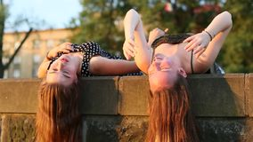 Two girls lying and talking on a stone slab with long hair hanging down. Beautiful soft light at sunset. stock video