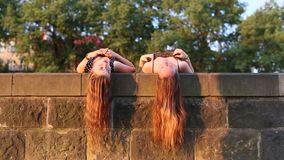 Two  girls lying and talking on a stone slab with long hair hanging down. Beautiful soft light at sunset. stock footage