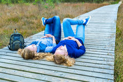 Two girls lying on their backs in nature. Two caucasian teenage girls lying on their backs on wooden path in park Stock Photos