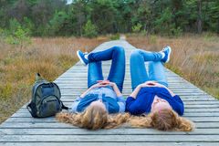 Two girls lying on their backs on wooden path in nature. Two teenage sisters lying on their backs on wooden path in nature Stock Photo