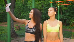 Two girls make merry fitness selfie. Sports figures and good mood. Slow Motion, shot 100 fps stock video footage