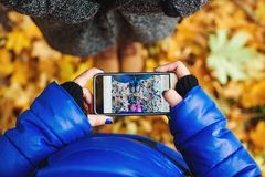 Two girls make a photo of shoes by phone in autumn park. Lifestyle and technology concept. royalty free stock photos