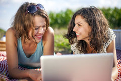 Two girls make a picnic and check computer Stock Photo