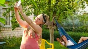 Two girls make selfie. Two girls make selfie in the garden near the house stock video