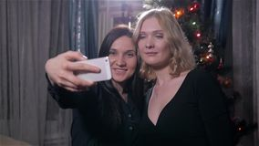 Two Girls Make Selfie Near The Green Christmas Tree. New Year Celebration. Slow Motion, HD stock video