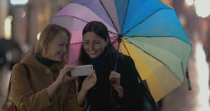 Two girls makes selfie on rainy day. Two young girls with multicolored umbrella makes selfie on the street on rainy day, people are passing by stock video