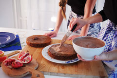 Two girls making a cake on the kitchen. Womens hands, causing the chocolate cream Royalty Free Stock Photos