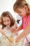 Two Girls Making Cupcakes In Kitchen Stock Photo