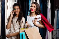 Two girls making shopping in mall. One speaking on phone. Two young beautiful girls making shopping, smiling, holding purchases in mall. One of them speaking on Royalty Free Stock Photos