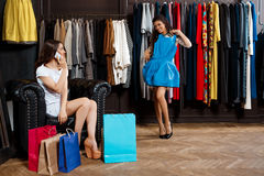 Two girls making shopping in mall. One speaking on phone. Two young beautiful girls making shopping, smiling in mall. One of them speaking on phone Royalty Free Stock Images
