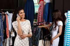 Two girls making shopping in mall. One speaking on phone. Two young beautiful girls making shopping in mall. One of them speaking on phone Royalty Free Stock Images