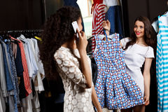 Two girls making shopping in mall. One speaking on phone. Two young beautiful girls making shopping in mall. One of them speaking on phone Stock Photo