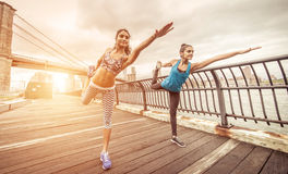 Two girls making stretching in Brooklyn pier at morning time. Brooklyn bridge and Manhattan skyline in the background stock photo